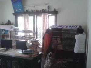 Nandhini, Sita, and Raja work together to move a bookshelf.